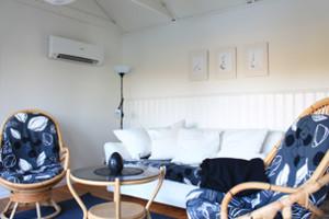 Das Wohnzimmer des Ferienhauses mit Schlafcouch, Kamin und Seeblick.