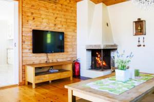 Schweden Ferienhaus am See mit offenem Kamin im Wohnzimmer und deutschem Fernsehen.