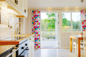 Seeblick aus der Küche unseres Schweden Ferienhauses mit Geschirrspüler und großer Terrasse mit Grill.