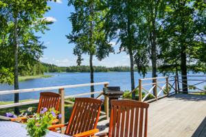 Der Blick von der Terrasse unseres Schweden Ferienhauses auf den See Saljen mit Booten und Badestelle.